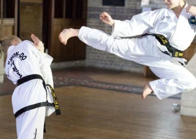 UKTD Black Belts girls Jade and Ellie demonstrating Taekwon-Do flying kicking and dodging defence