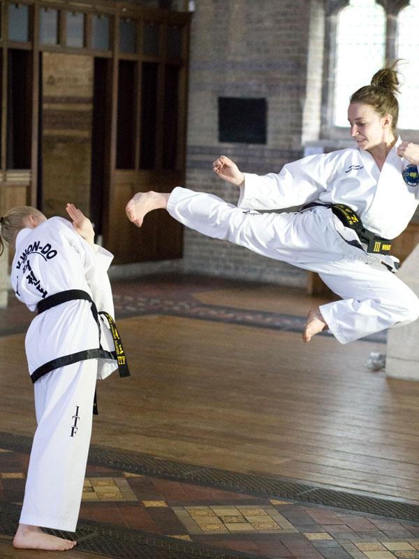 UKTD Black Belts girls Jade and Ellie demonstrating Taekwon-Do flying kicking and dodging defence